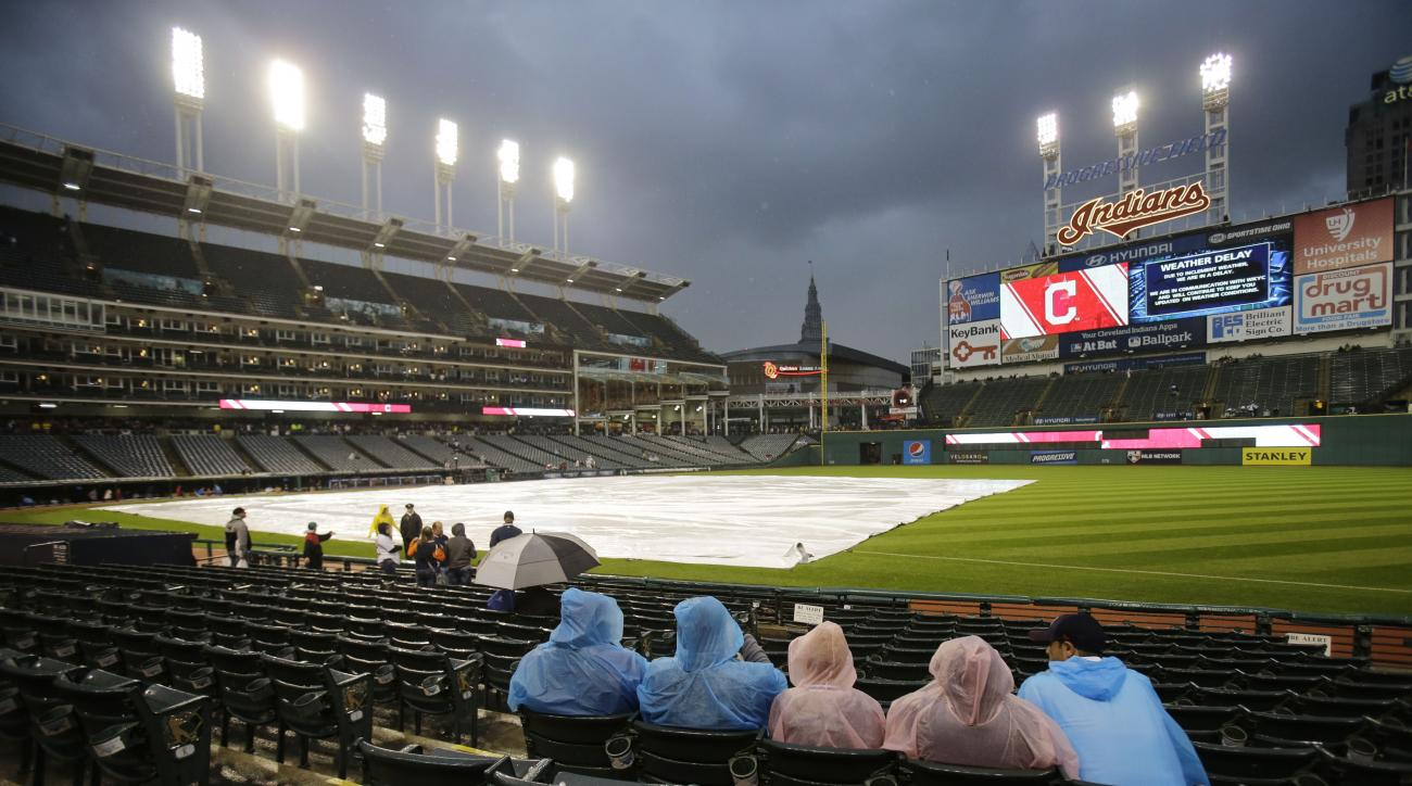 Fans wait during a rain delay in a baseball game between the Detroit Tigers and the Cleveland Indians, Saturday, Sept. 12, 2015, in Cleveland. (AP Photo/Tony Dejak)