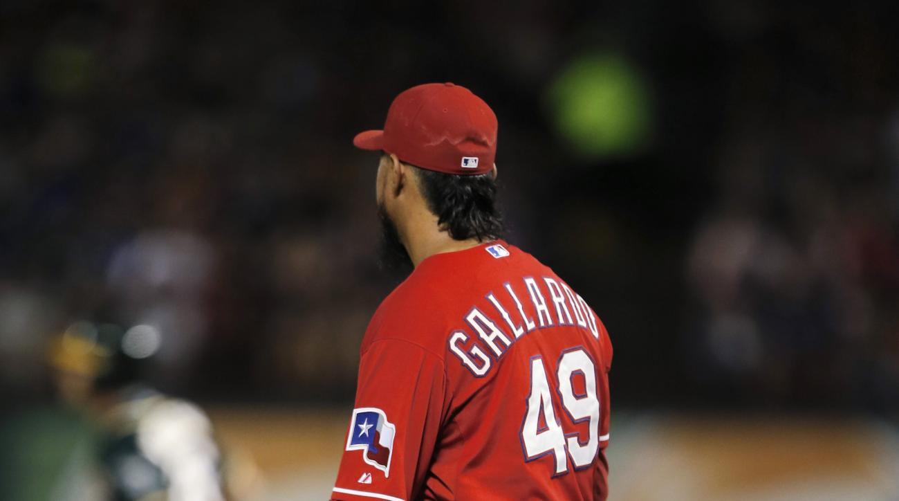 Texas Rangers starting pitcher Yovani Gallardo (49) watches as Oakland Athletics third baseman Danny Valencia, background, circles the bases on his two-run home run during the fifth inning of a baseball game, Saturday, Sept. 12, 2015, in Arlington, Texas.