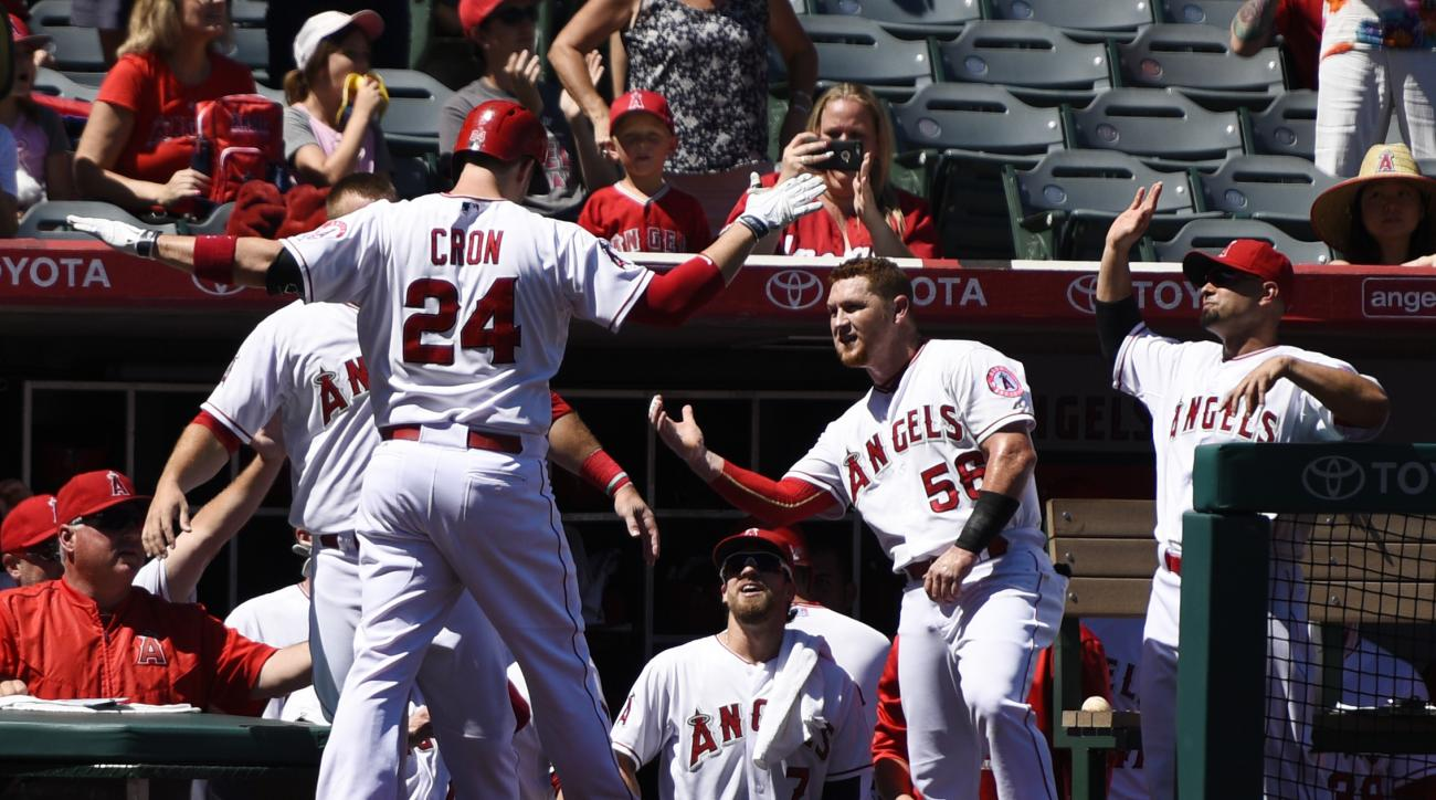 Los Angeles Angels' C.J. Cron (24) celebrates with the dugout after hitting a solo home run off Houston Astros starting pitcher Mike Fiers during the second inning of a baseball game in Anaheim, Calif., Sunday, Sept. 13, 2015. (AP Photo/Kelvin Kuo)