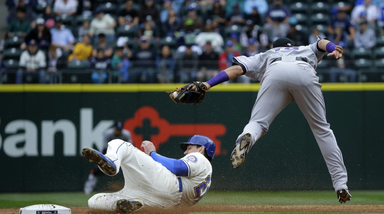 Seattle Mariners' Logan Morrison, left, is caught stealing second base by Colorado Rockies shortstop Cristhian Adames, right, in the third inning of a baseball game, Sunday, Sept. 13, 2015, in Seattle. (AP Photo/Ted S. Warren)
