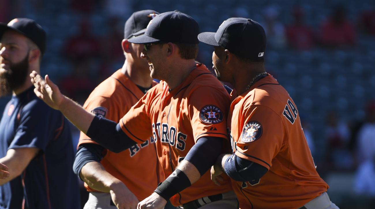 Houston Astros' Jed Lowrie, left, celebrates with Luis Valbuena, right, after a baseball game against the Los Angeles Angels in Anaheim, Calif., Sunday, Sept. 13, 2015. The Astros won 5-3. (AP Photo/Kelvin Kuo)