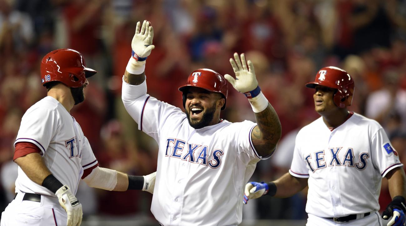 Texas Rangers' Prince Fielder, center, is congratulated by Mitch Moreland, left, and Adrian Beltre, right, after Fielder's two-run home run that scored Beltre in the eighth inning of a baseball game against the Houston Astros Monday, Sept. 14, 2015, in Ar