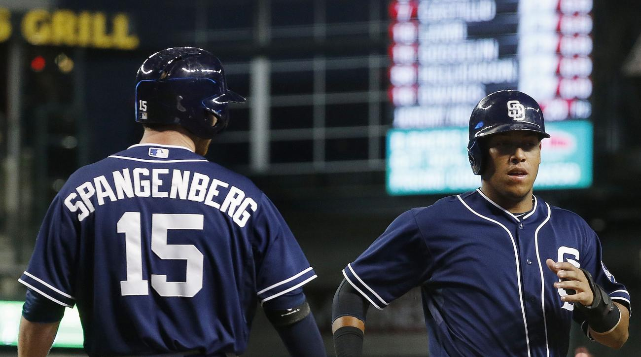 San Diego Padres' Yangervis Solarte, right, shakes hands with Cory Spangenberg (15) after Solarte scored a run against the Arizona Diamondbacks during the first inning of a baseball game Monday, Sept. 14, 2015, in Phoenix. (AP Photo/Ross D. Franklin)