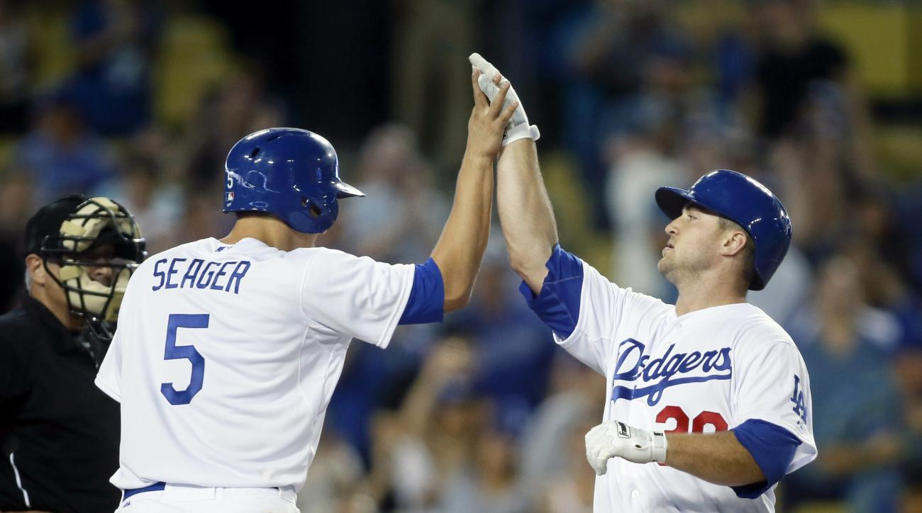 Los Angeles Dodgers' Scott Schebler, right, celebrates hitting a two-run home run and driving in Corey Seager, left, against the Colorado Rockies during the eighth inning of a baseball game, Monday, Sept. 14, 2015, in Los Angeles. (AP Photo/Danny Moloshok