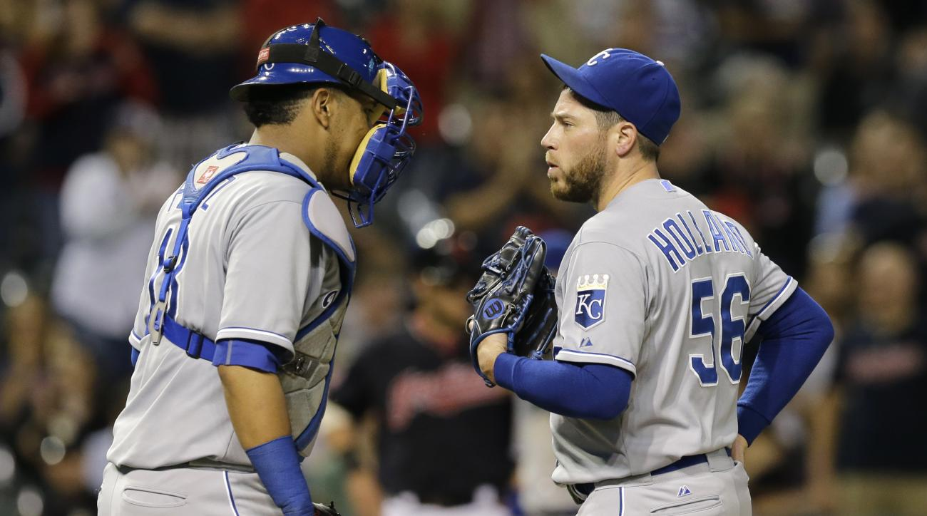Kansas City Royals catcher Salvador Perez, left, talks with relief pitcher Greg Holland during the ninth inning of a baseball game against the Cleveland Indians, Tuesday, Sept. 15, 2015, in Cleveland. The Royals won 2-0. (AP Photo/Tony Dejak)