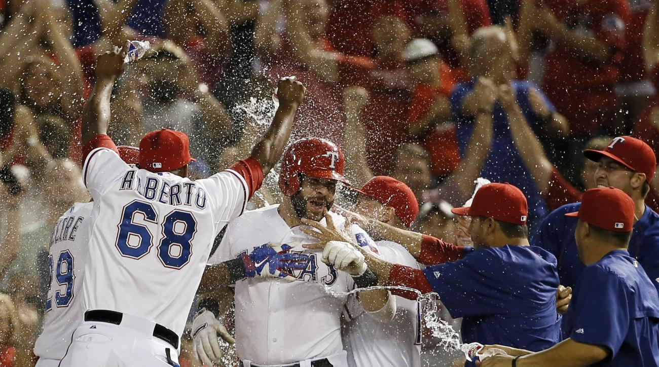 Texas Rangers' Hanser Alberto (68) and the rest of the team celebrate with Mitch Moreland, center, after Moreland hit an RBI sacrifice fly off Houston Astros relief pitcher Will Harris during the ninth inning of a baseball game Tuesday, Sept. 15, 2015, in