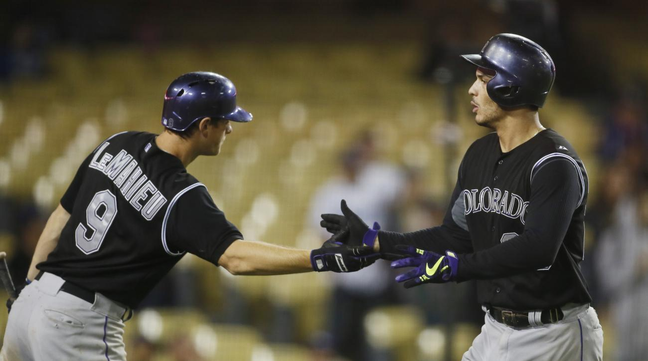 Colorado Rockies' Nolan Arenado, right, celebrates with DJ LeMahieu after hitting a solo home run against the Los Angeles Dodgers during the 16th inning of a baseball game, early Wednesday, Sept. 16, 2015, in Los Angeles. (AP Photo/Danny Moloshok)