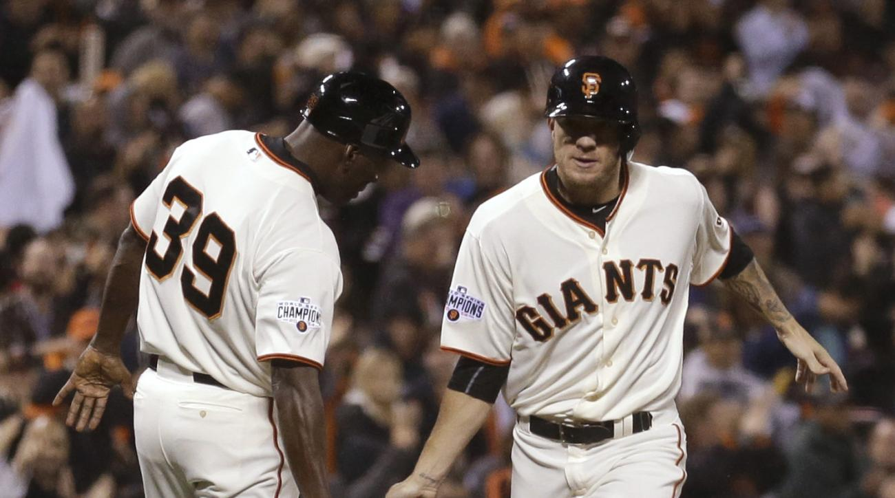San Francisco Giants pitcher Jake Peavy, right, is congratulated by third base coach Roberto Kelly (39) after hitting a home run off Cincinnati Reds' Collin Balester during the fourth inning of a baseball game Wednesday, Sept. 16, 2015, in San Francisco.