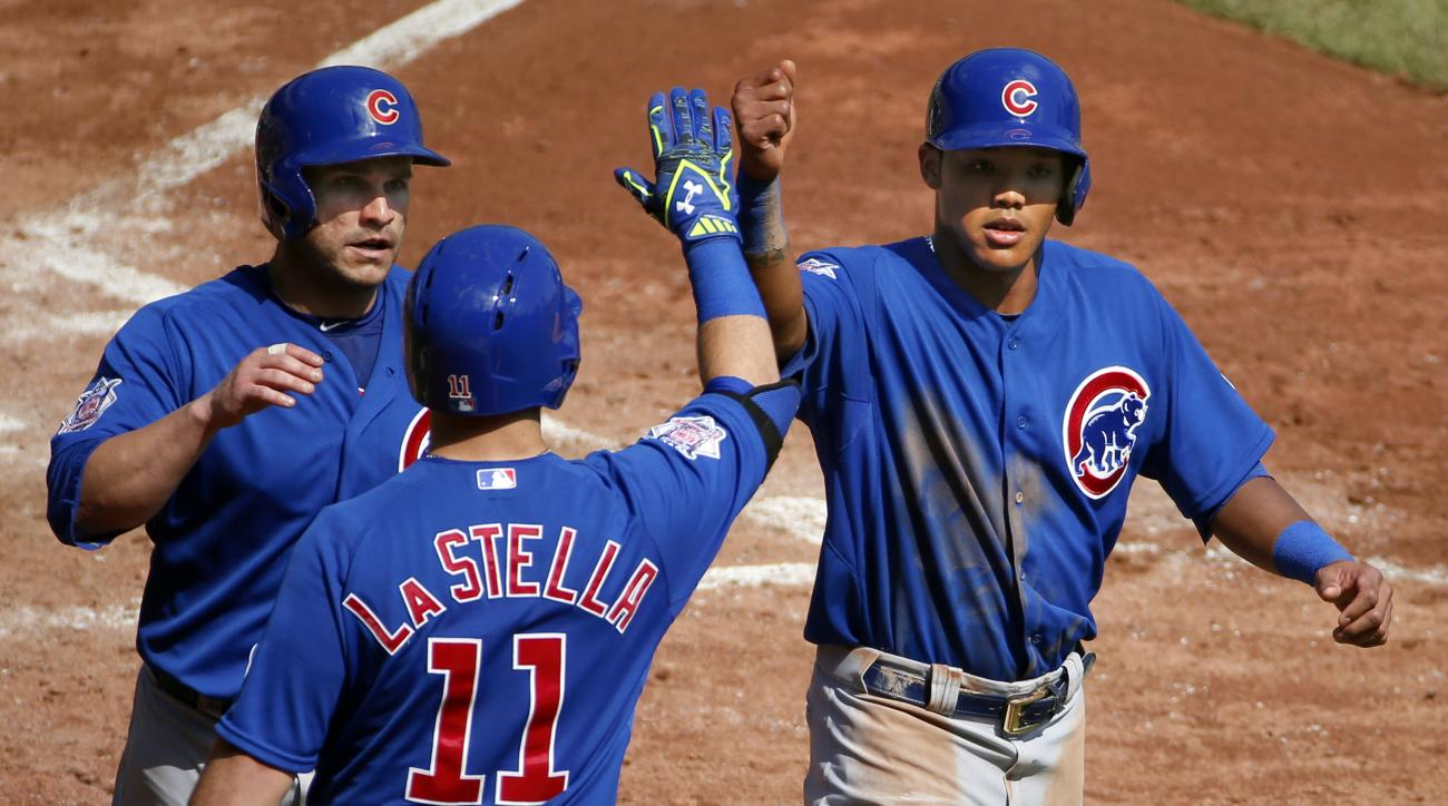 Chicago Cubs' Addison Russell, right, and Miguel Montero, left, celebrate with teammate Tommy La Stella (11) after scoring on a double by relief pitcher Clayton Richard off Pittsburgh Pirates relief pitcher Joe Blanton in the fifth inning of a baseball ga