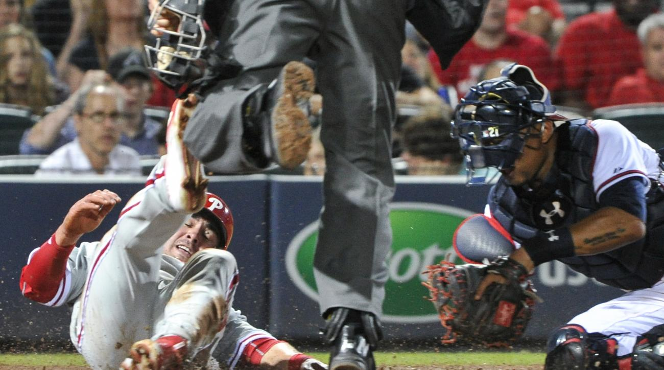 Philadelphia Phillies' Chase d'Arnaud, left, is out after a collision at home plate with Atlanta Braves catcher Christian Bethancourt, right, during the seventh inning of a baseball game Friday, Sept. 18, 2015, in Atlanta. (AP Photo/John Amis)