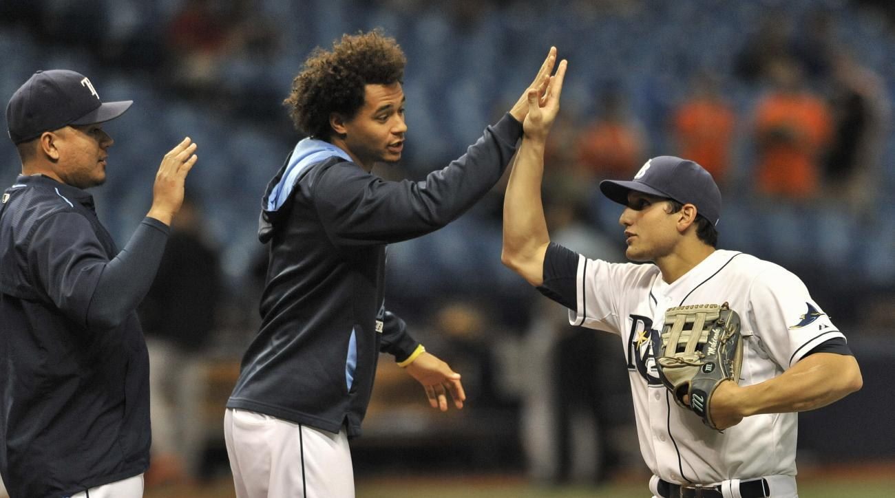 Tampa Bay Rays' Erasmo Ramirez, left, Chris Archer, center, and Mikie Mahtook celebrate a 8-6 win over the Baltimore Orioles during a baseball game Friday, Sept. 18, 2015, in St. Petersburg, Fla. Mahtook went five for five at the plate, hitting two double