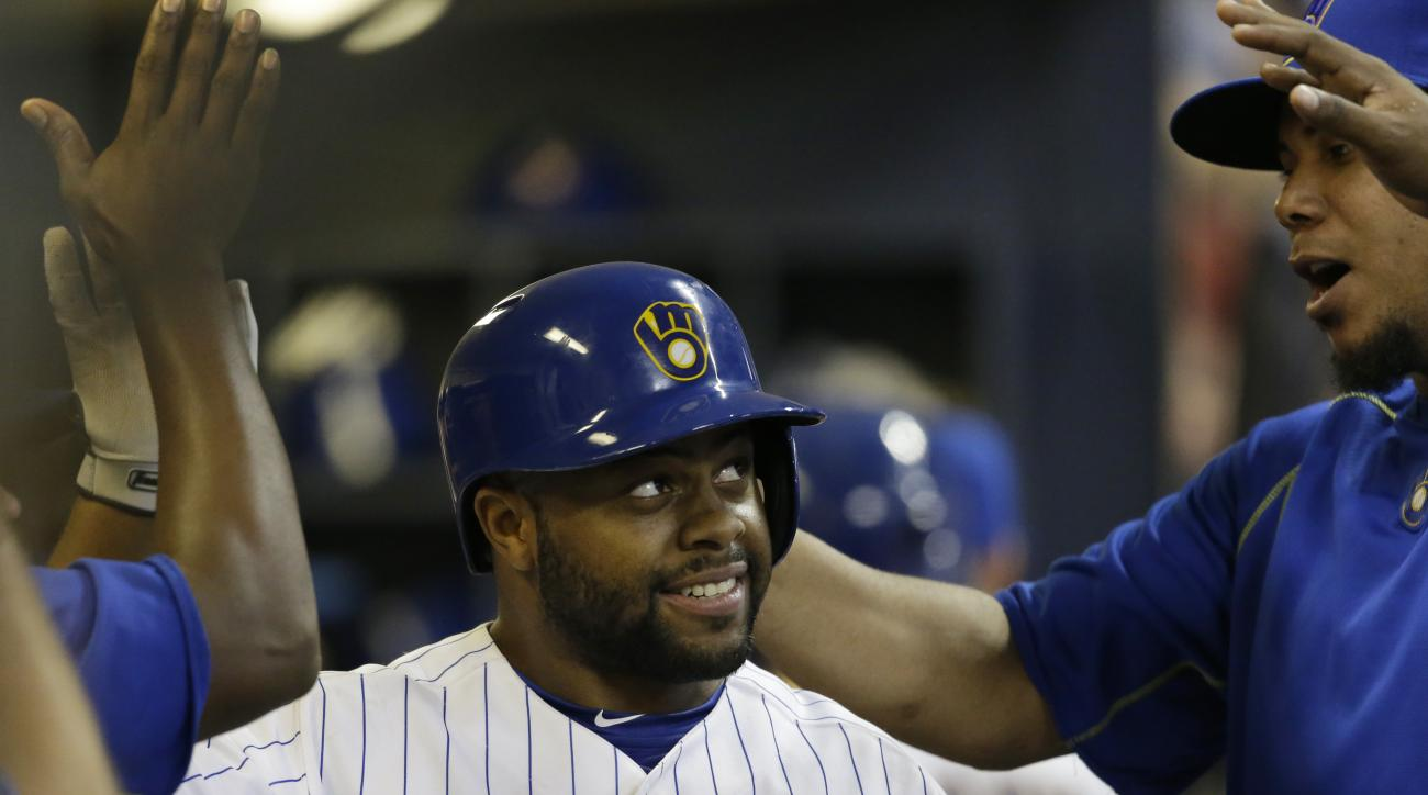 Milwaukee Brewers' Jason Rogers receives congratulations in the dugout after his home run against the Cincinnati Reds during the eighth inning a baseball game Friday, Sept. 18, 2015, in Milwaukee. (AP Photo/Jeffrey Phelps)