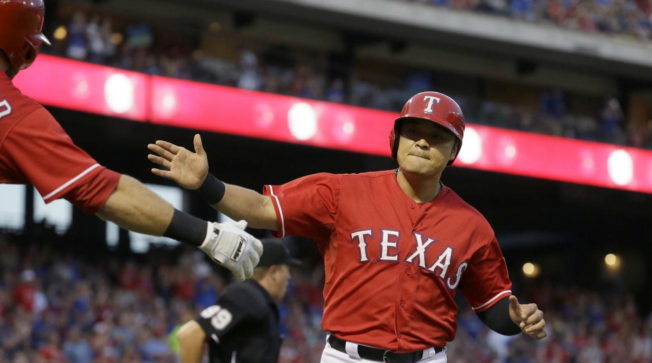 Texas Rangers Shin-Soo Choo, of South Korea, celebrates scoring from third base on an RBI-single by teammate Mike Napoli during the first inning of a baseball game against the Seattle Mariners in Arlington, Texas, Saturday, Sept. 19, 2015. (AP Photo/LM Ot