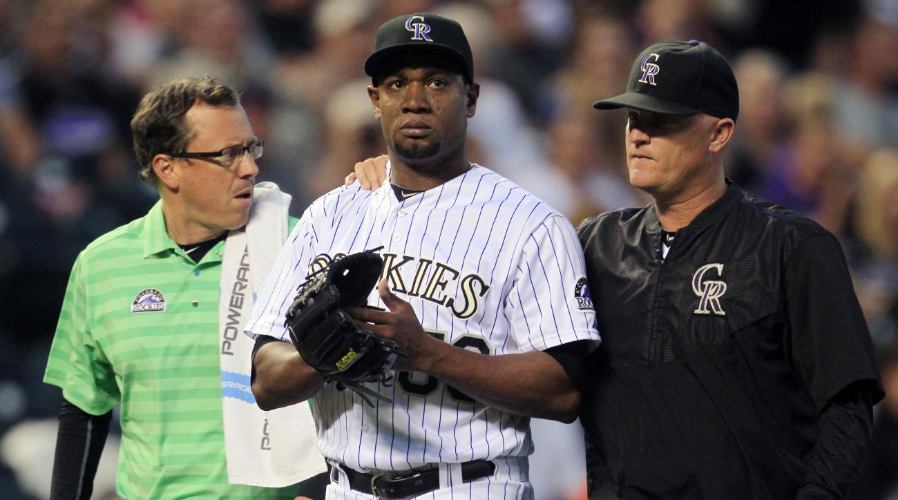 Colorado Rockies assistant trainer Scott Gehret, left, escorts starting pitcher Yohan Flande, center, from the game with pitching coach Stephen Foster, after Flande was hit in the left leg by San Diego Padres batter Jedd Gyorko's line drive in the third i