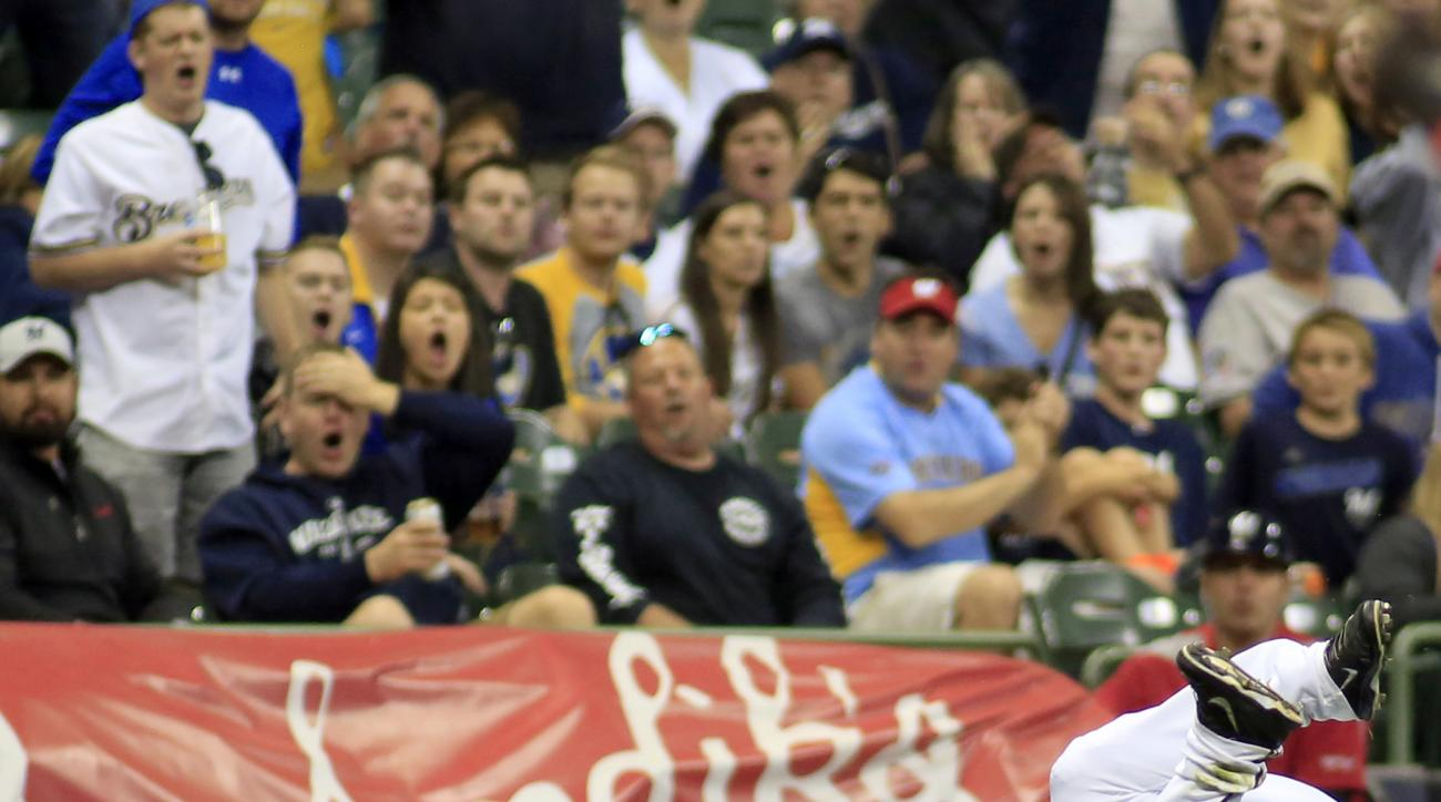 Milwaukee Brewers third baseman Elian Herrera, left, and left fielder Shane Peterson react after colliding while trying to catch an RBI single from Cincinnati Reds' Skip Schumaker during the eighth inning of a baseball game Saturday, Sept. 19, 2015, in Mi