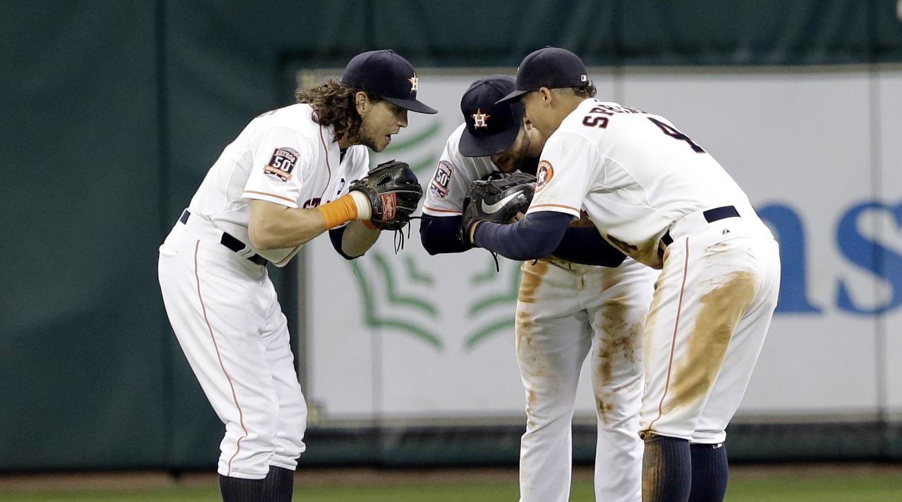 Houston Astros' Colby Rasmus, left, Jake Marisnick, center, and George Springer bow to one another after beating the Oakland Athletics 10-6 in a baseball game Saturday, Sept. 19, 2015, in Houston. (AP Photo/Pat Sullivan)