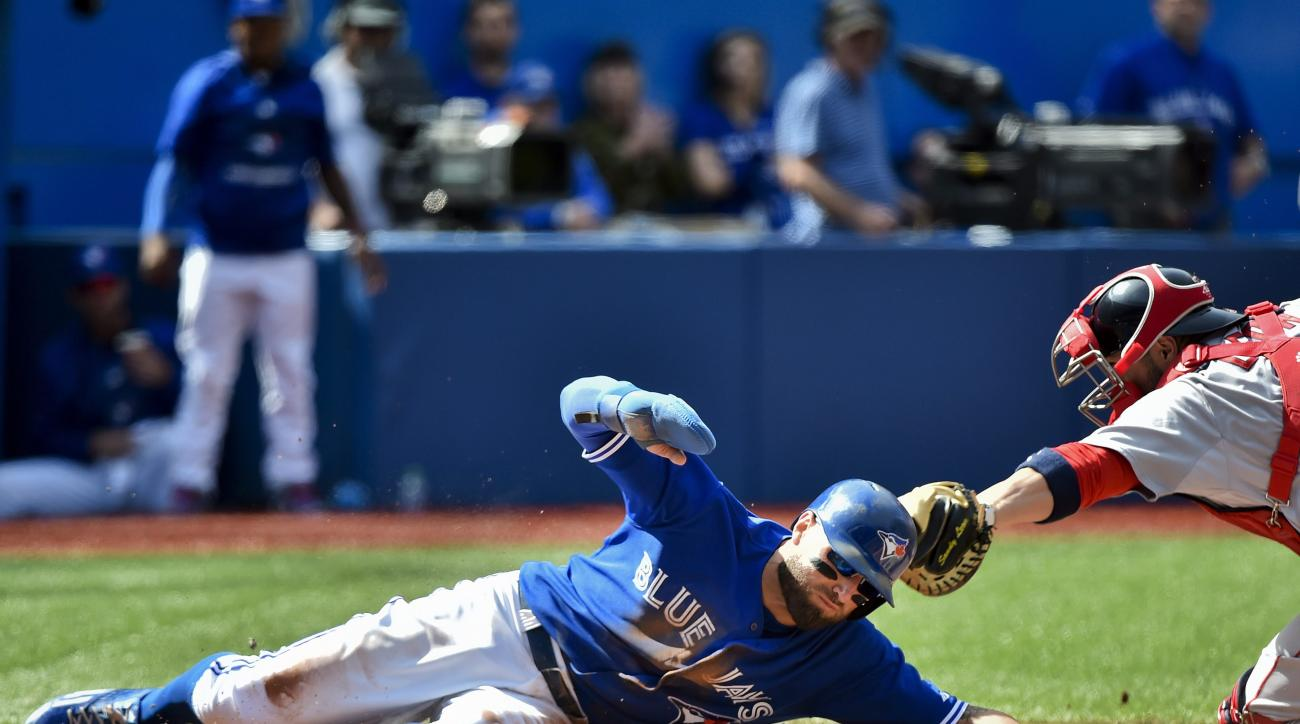 Toronto Blue Jays' Kevin Pillar, left, slides safe past Boston Red Sox catcher Sandy Leon at home plate to score a run during the second inning of a baseball game in Toronto on Sunday, Sept. 20, 2015. (Nathan Denette/The Canadian Press via AP)