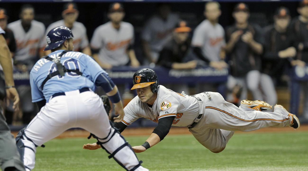 Baltimore Orioles' Steve Pearce dives towards home plate before the throw to Tampa Bay Rays catcher J.P. Arencibia (40) during the eighth inning of a baseball game Sunday, Sept. 20, 2015, in St. Petersburg, Fla.  Pearce scored on third baseman Evan Longor