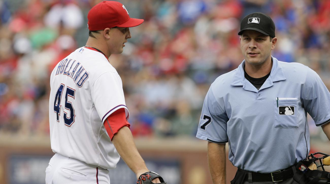 Texas Rangers starting pitcher Derek Holland (45) discusses a call with umpire Ben May (97) during the second inning of a baseball game against the Seattle Mariners in Arlington, Texas, Sunday, Sept. 20, 2015. (AP Photo/LM Otero)