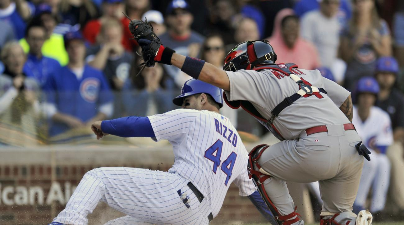 St. Louis Cardinals catcher Yadier Molina (4) holds his glove up after tagging out Chicago Cubs' Anthony Rizzo (44), at home plate during the eighth inning of a baseball game Sunday, Sept. 20, 2015 in Chicago. St. Louis won 4-3. (AP Photo/Paul Beaty)
