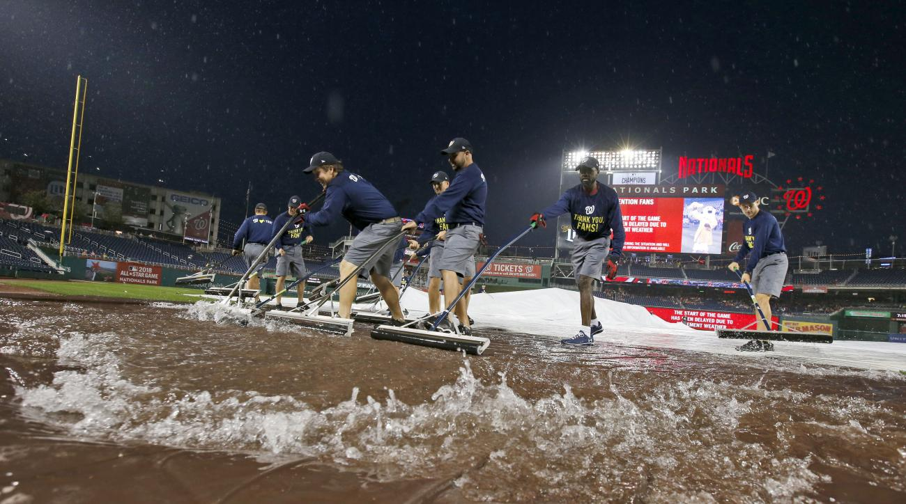 Members of the grounds crew squeegee rainwater off the tarp before a baseball game between the Washington Nationals and the Baltimore Orioles at Nationals Park, Monday, Sept. 21, 2015, in Washington. (AP Photo/Alex Brandon)