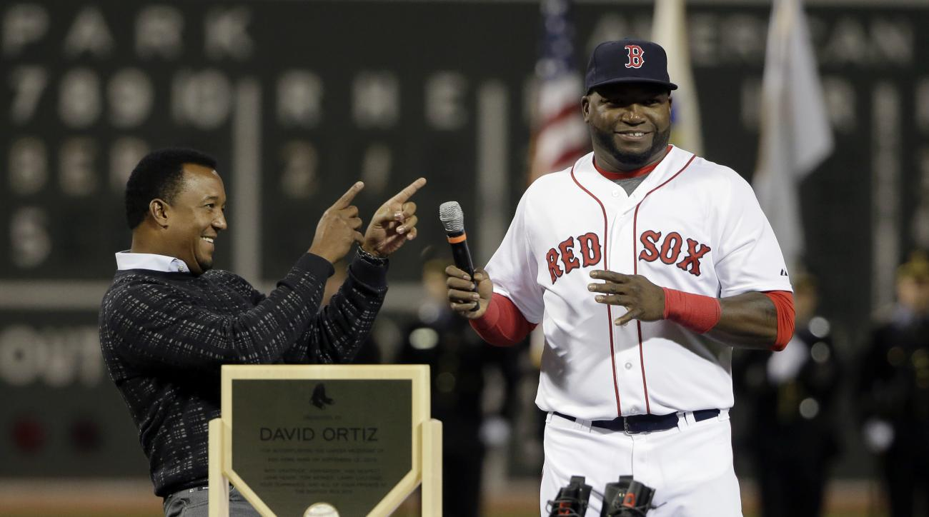 Former Boston Red Sox pitcher Pedro Martinez, left, smiles and points toward Red Sox's David Ortiz as Ortiz takes the microphone during ceremonies held to honor his 500 career home runs before a baseball game against the Tampa Bay Rays, Monday, Sept. 21,