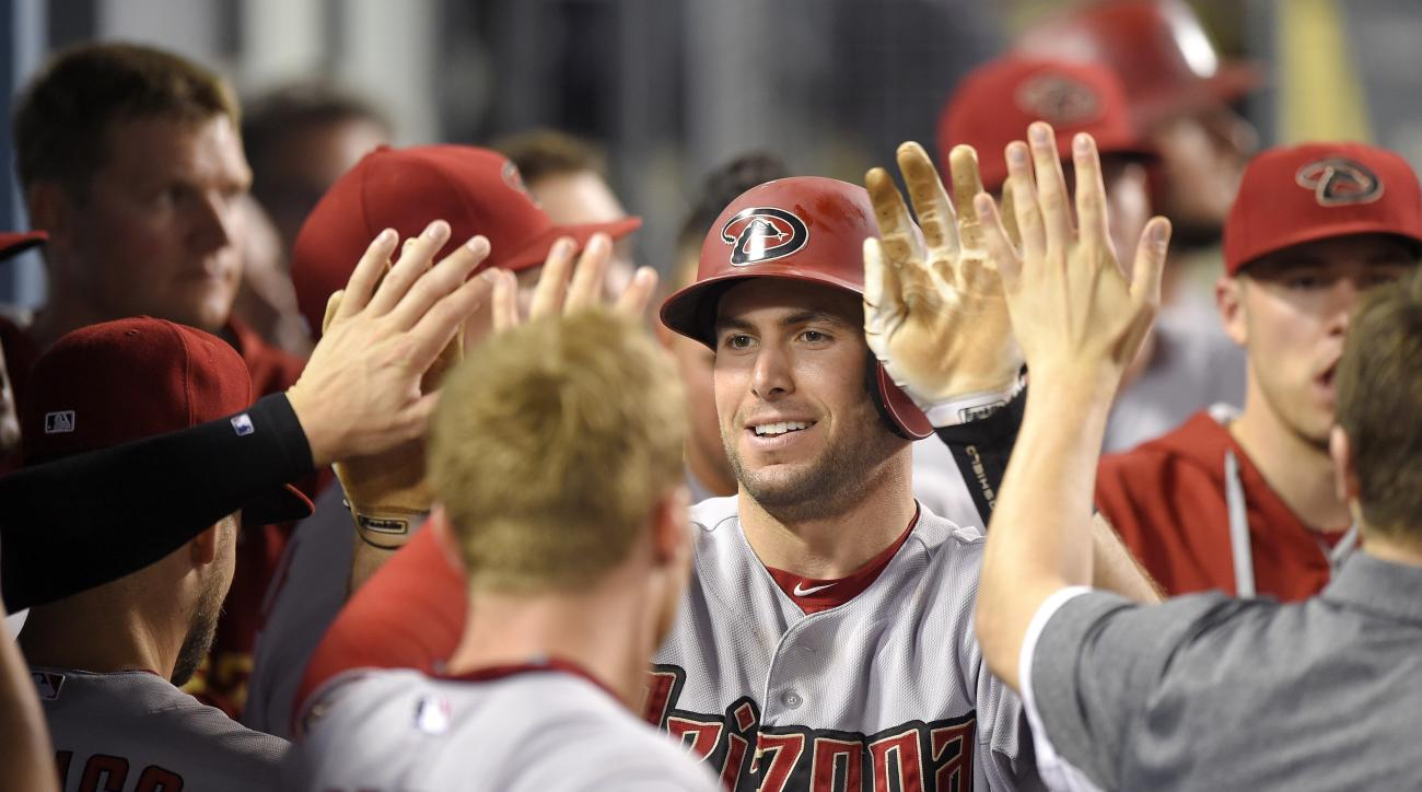 Arizona Diamondbacks' Paul Goldschmidt is congratulated by teammates after hitting a solo home run during the eighth inning of a baseball game against the Los Angeles Dodgers, Monday, Sept. 21, 2015, in Los Angeles. (AP Photo/Mark J. Terrill)