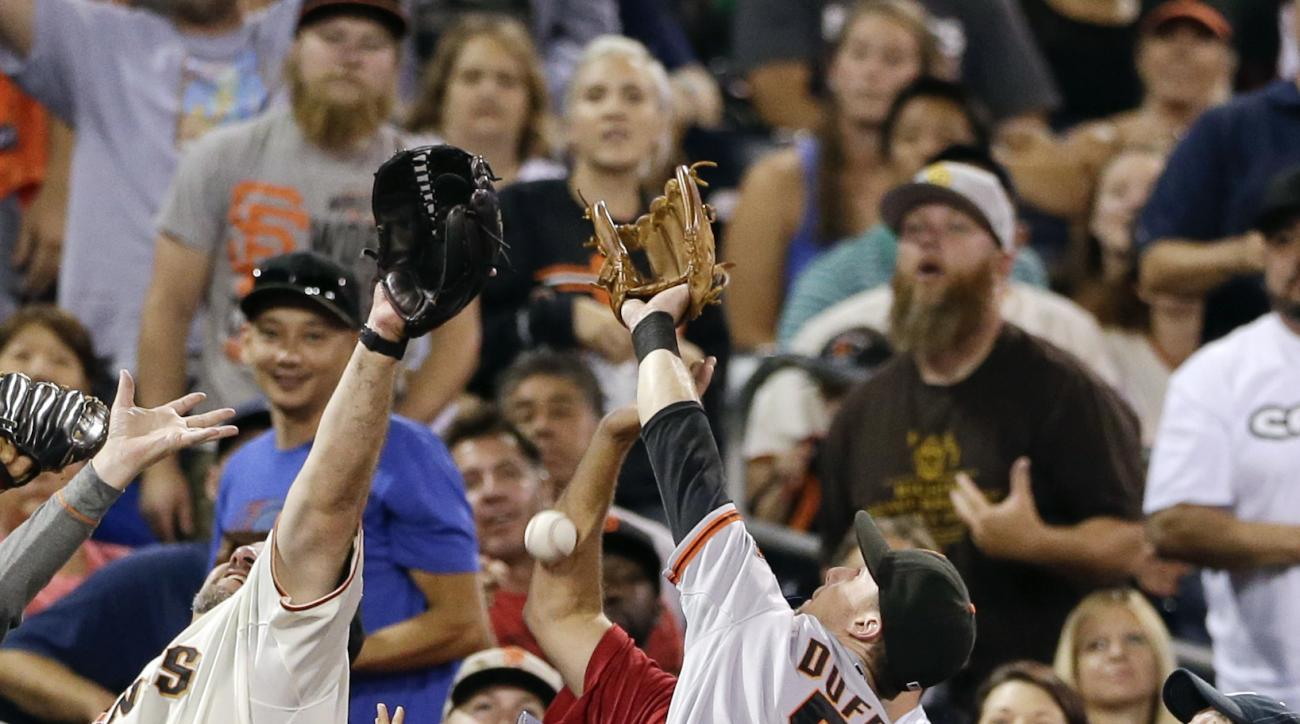 San Francisco Giants third baseman Matt Duffy collides with fans as he misses a foul ball hit by San Diego Padres' Jedd Gyorko during the fourth inning of a baseball game Tuesday, Sept. 22, 2015, in San Diego. (AP Photo/Gregory Bull)