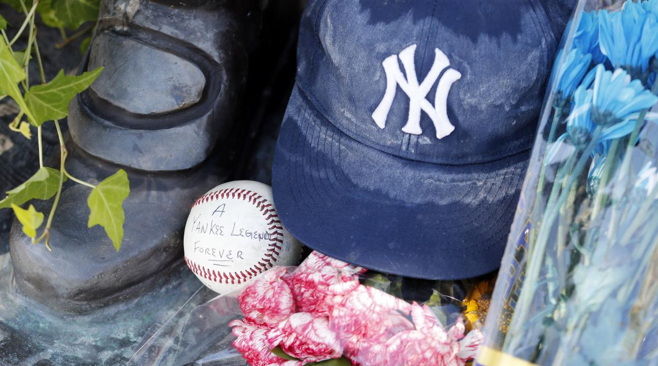 A ball placed by Aaron Bertone, 9, of Clifton, N.J., is seen at the feet of a statue of former New York Yankees hall of fame catcher Yogi Berra outside of the Yogi Berra Museum, Wednesday, Sept. 23, 2015, in Little Falls, N.J. Berra died Tuesday at the ag