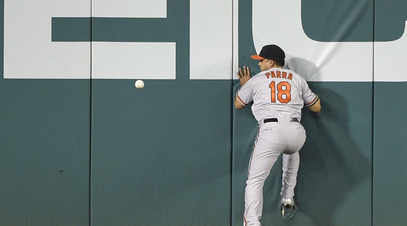 Baltimore Orioles right fielder Gerardo Parra (18) runs into the wall as a ball hit for a double by Washington Nationals' Anthony Rendon bounces around during the first inning of an interleague baseball game, Wednesday, Sept. 23, 2015, in Washington. (AP