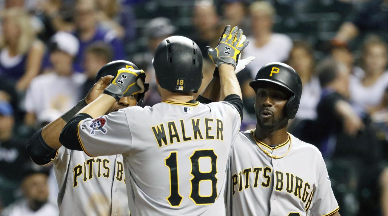 Pittsburgh Pirates' Neil Walker is congratulated at the plate by teammates Starling Marte, left, and Andrew McCutchen (22) after hitting a three run homer against Colorado Rockies starting pitcher Christian Bergman during the third inning of a baseball ga