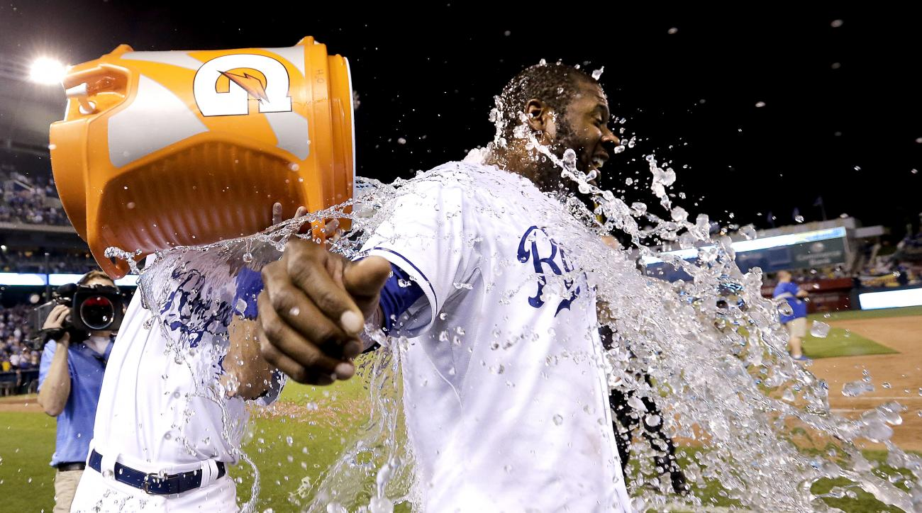 Kansas City Royals' Lorenzo Cain is doused by Drew Butera after Cain hit a single to score the game-winning run during the 10th inning of a baseball game against the Seattle Mariners on Wednesday, Sept. 23, 2015, in Kansas City, Mo. The Royals won 4-3. (A