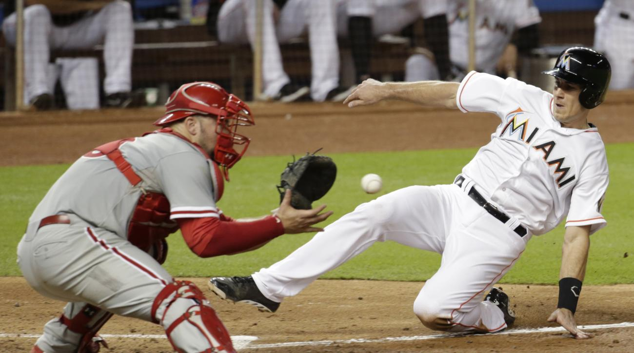 Miami Marlins' J.T. Realmuto slides as Philadelphia Phillies catcher Cameron Rupp takes the throw during the seventh inning of a baseball game, Thursday, Sept. 24, 2015, in Miami. Realmuto was tagged out on the play. (AP Photo/Lynne Sladky)
