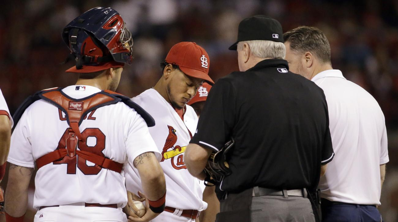 St. Louis Cardinals starting pitcher Carlos Martinez, center, prepares to leave a baseball game against the Milwaukee Brewers during the first inning on Friday, Sept. 25, 2015, in St. Louis. Martinez was removed with an apparent injury after throwing seve