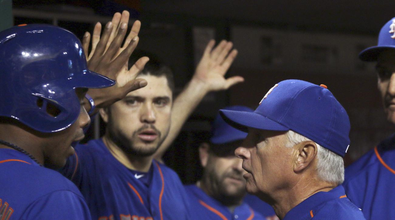 New York Mets' Curtis Granderson gets congratulations by manager Terry Collins, right, after scoring against the Cincinnati Reds during the seventh inning of a baseball game in Cincinnati, Friday, Sept. 25, 2015. (AP Photo/Tom Uhlman)
