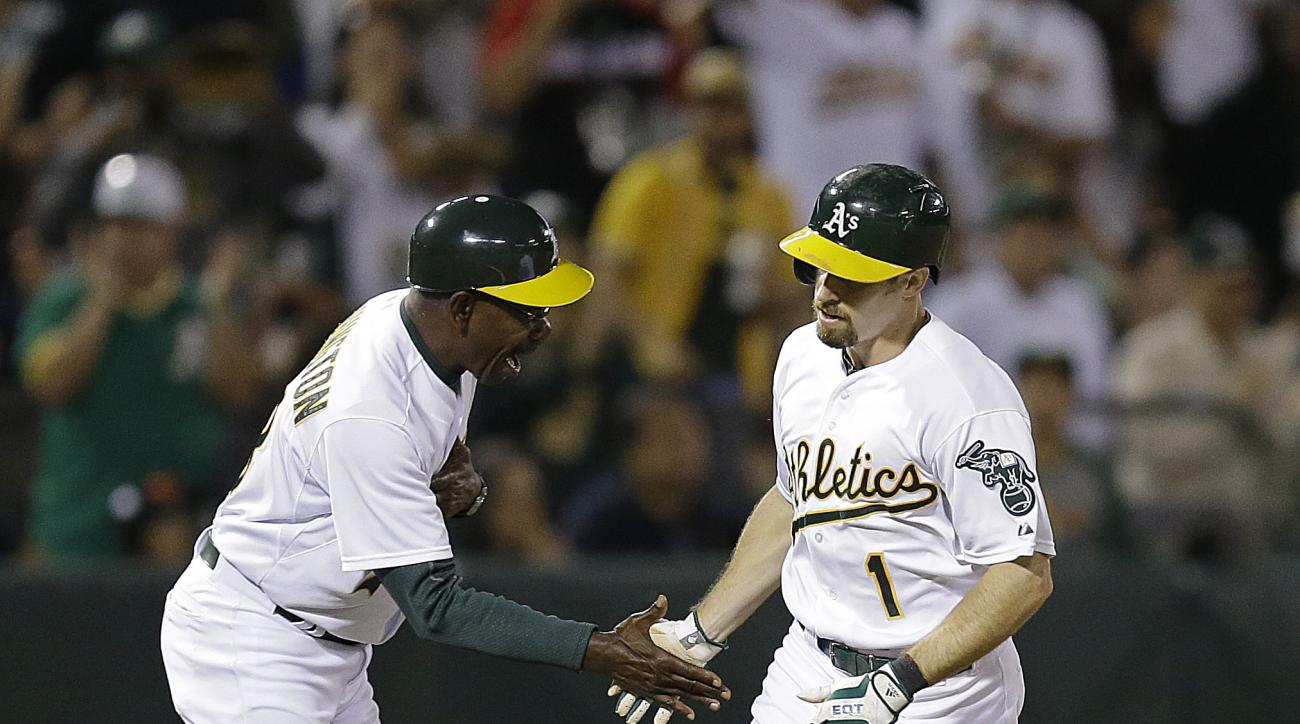 Oakland Athletics' Billy Burns, right, is congratulated by third base coach Ron Washington after hitting a home run against the San Francisco Giants during the third inning of a baseball game Friday, Sept. 25, 2015, in Oakland, Calif. (AP Photo/Ben Margot