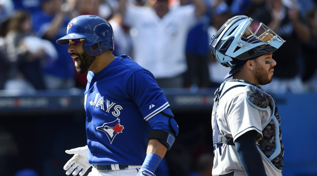 Toronto Blue Jays' Jose Bautista, left, celebrates behind Tampa Bay catcher Rene Rivera following his three-run home run in the first inning of a baseball game  agains the Tampa Bay Ray in Toronto, Saturday, Sept. 26, 2015. (Frank Gunn/The Canadian Press