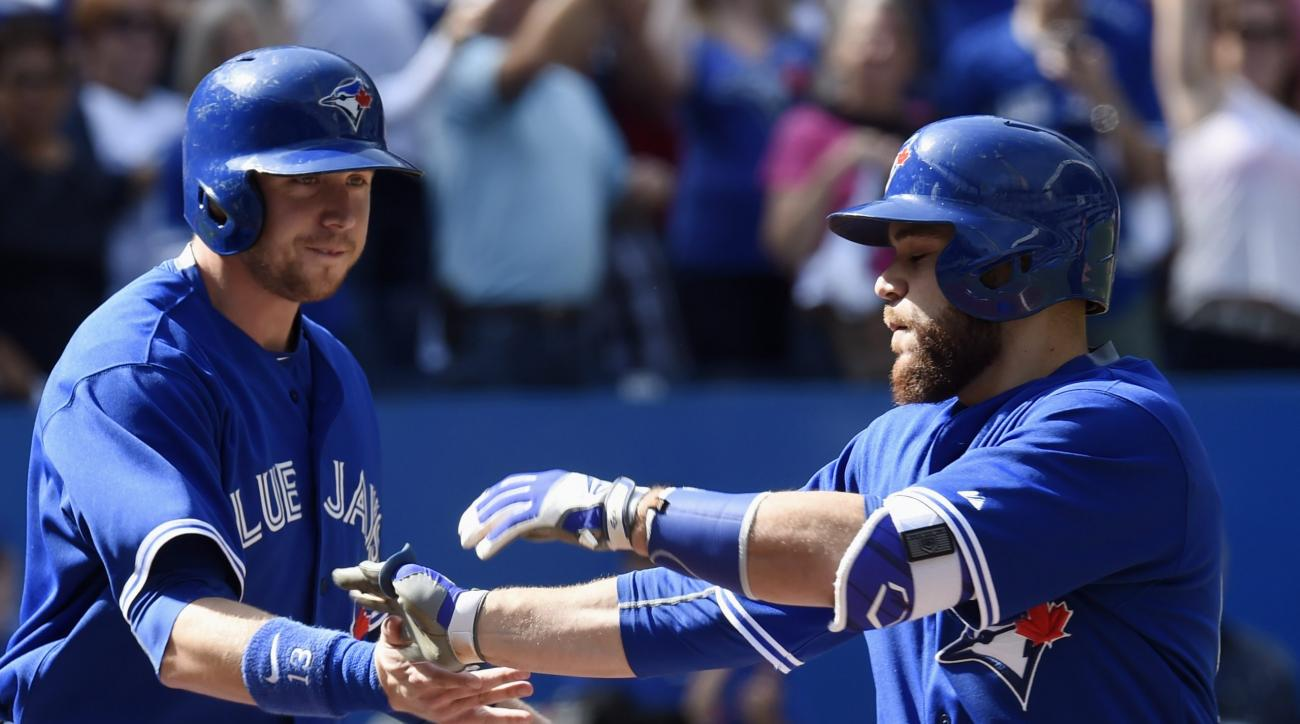 Toronto Blue Jays' Russell Martin, right, celebrates with teammate Justin Smoak, left, following a two-run home run during first inning of a baseball game against the Tampa Bay Rays in Toronto, Saturday, Sept. 26, 2015. (Frank Gunn/The Canadian Press via