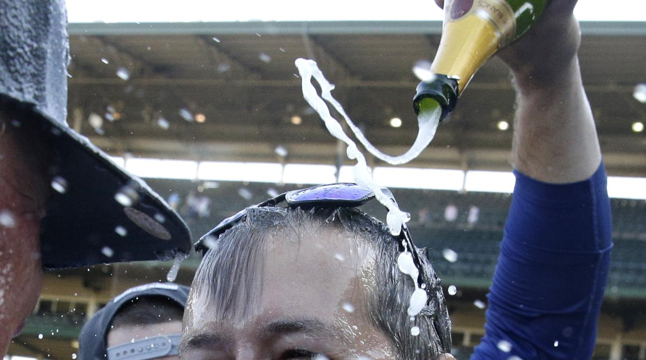 Chicago Cubs' Anthony Rizzo, back, pours champagne on team owner Thomas S. Ricketts as they celebrate the Chicago Cubs clinching a postseason berth after the Cubs' 4-0 loss to the Pittsburgh Pirates in a baseball game Saturday, Sept. 26, 2015, in Chicago.