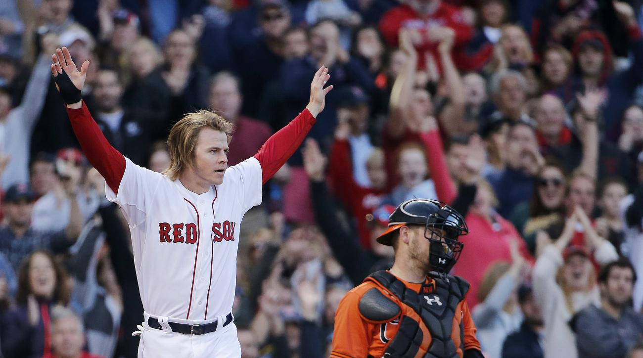 Boston Red Sox's Brock Holt, left, celebrates next to Baltimore Orioles' Matt Wieters after scoring on a double by Josh Rutledge during the fifth inning of a baseball game in Boston, Saturday, Sept. 26, 2015. (AP Photo/Michael Dwyer)
