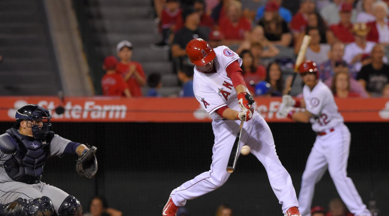 Los Angeles Angels' David Freese, center, hits a walk-off home run as Seattle Mariners catcher Jesus Sucre watches during the ninth inning of a baseball game, Saturday, Sept. 26, 2015, in Anaheim, Calif. The Angels won 3-2. (AP Photo/Mark J. Terrill)