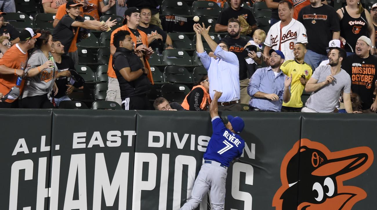 Toronto Blue Jays left fielder Ben Revere leaps for a three-home run hit by Baltimore Orioles Ryan Flaherty and loses his glove in the crowd in the second inning of a baseball game, Monday, Sept. 28, 2015, in Baltimore. (AP Photo/Gail Burton)
