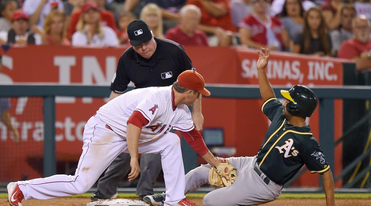 Oakland Athletics' Marcus Semien, right, is tagged out at third by Los Angeles Angels third baseman David Freese as he tried to make it from first to third on a single by Coco Crisp during the sixth inning of a baseball game, Monday, Sept. 28, 2015, in An