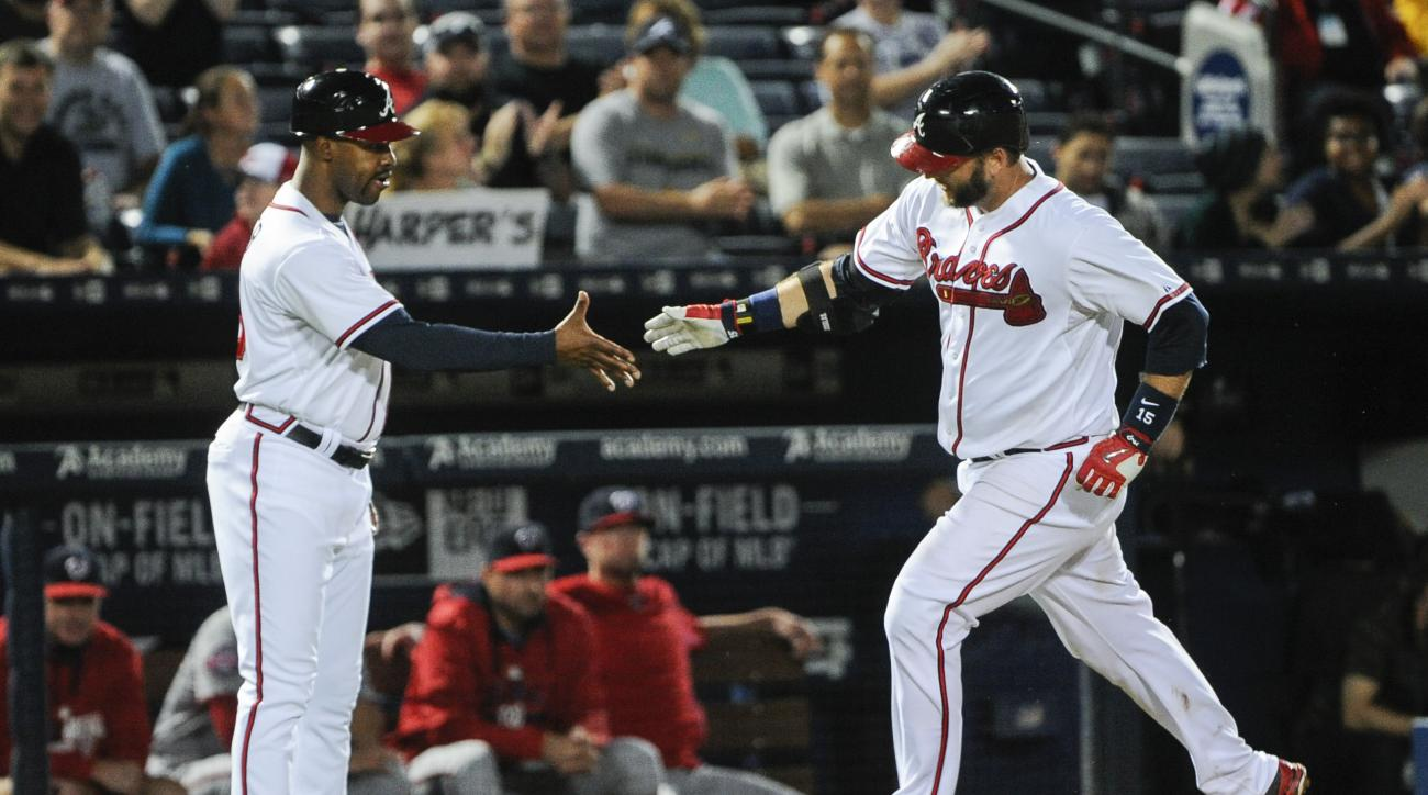 Atlanta Braves' A.J. Pierzynski rounds their base to congratulations by coach Bo Porter, left, during a home run against the Washington Nationals in the seventh inning of a baseball game, Tuesday, Sept. 29, 2015, in Atlanta. (AP Photo/John Amis)