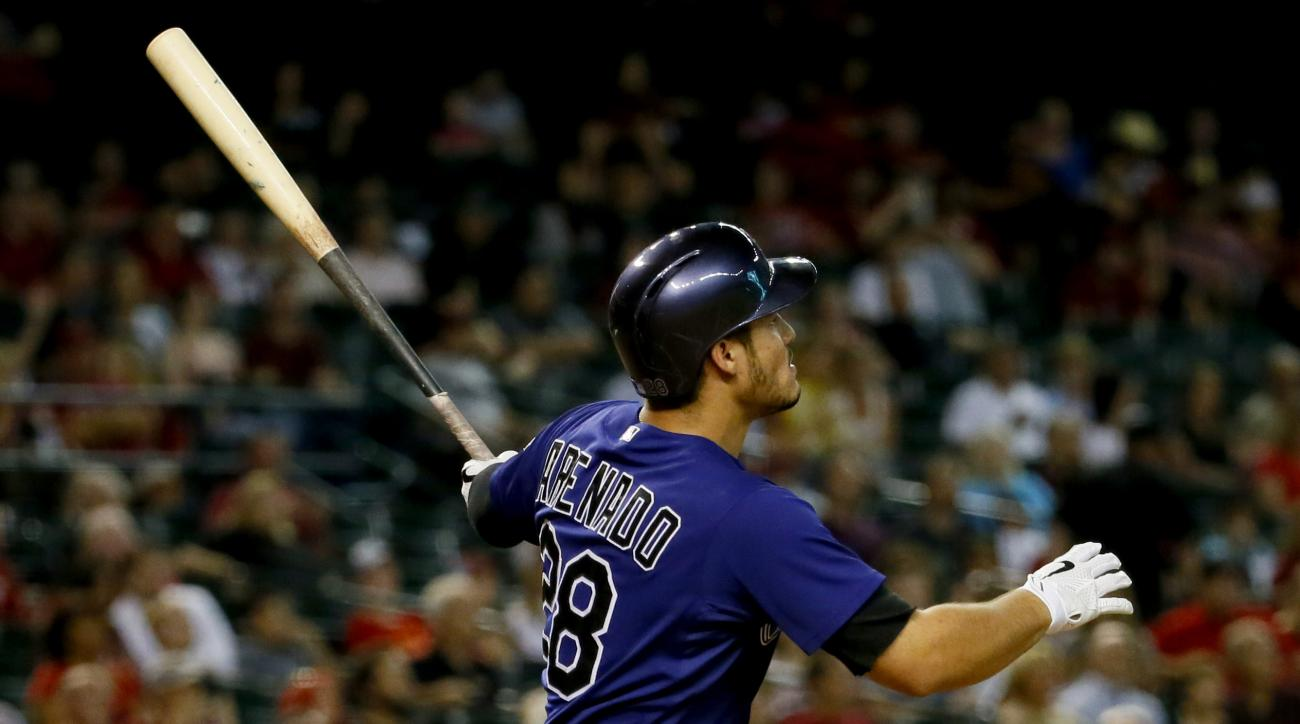 Colorado Rockies' Nolan Arenado follows through on an RBI sacrifice fly during the first inning of a baseball game against the Arizona Diamondbacks, Tuesday, Sept. 29, 2015, in Phoenix. (AP Photo/Matt York)