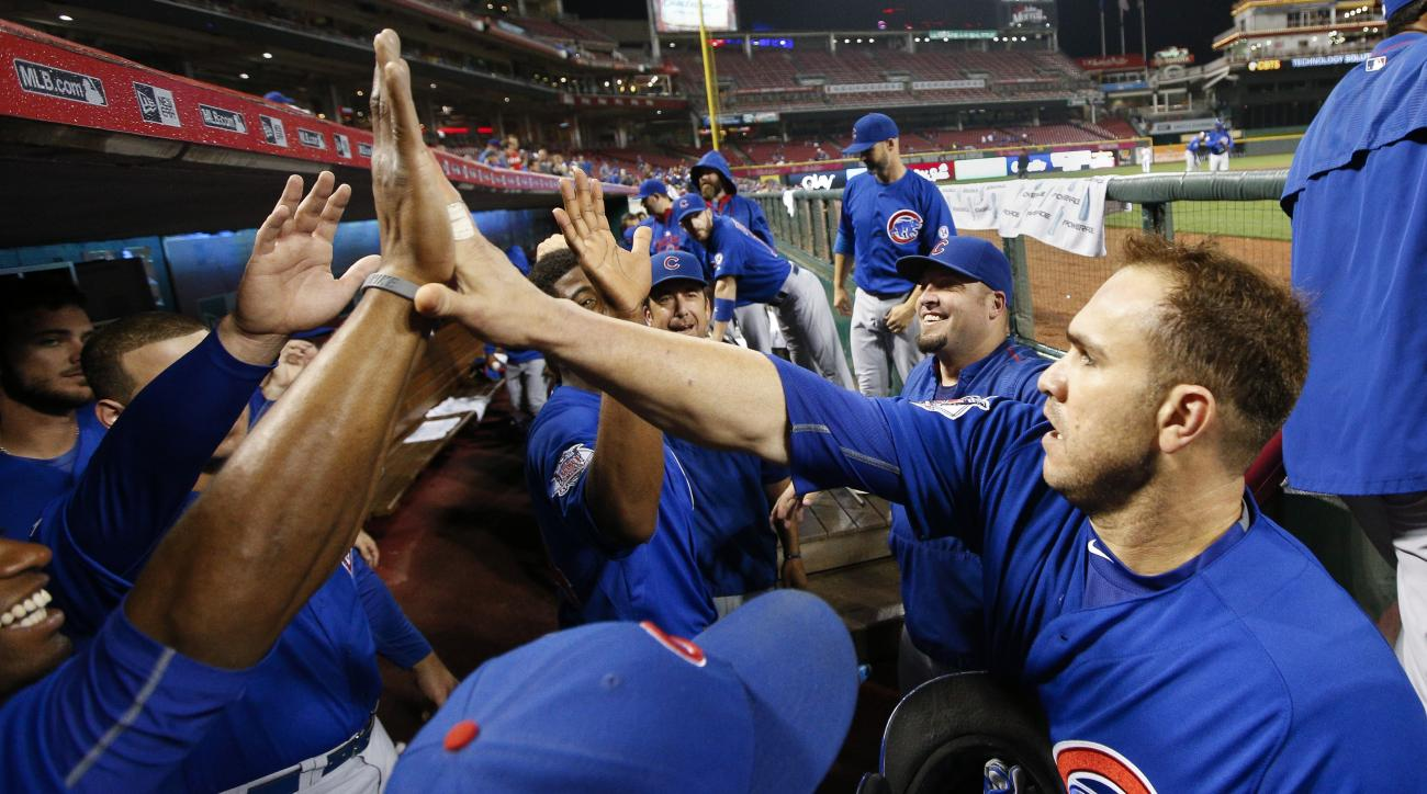 The Chicago Cubs celebrate in the dugout as Miguel Montero, right, enters after scoring on a RBI single hit by Javier Baez in the first inning of a baseball game, Tuesday, Sept. 29, 2015, in Cincinnati. (AP Photo/John Minchillo)