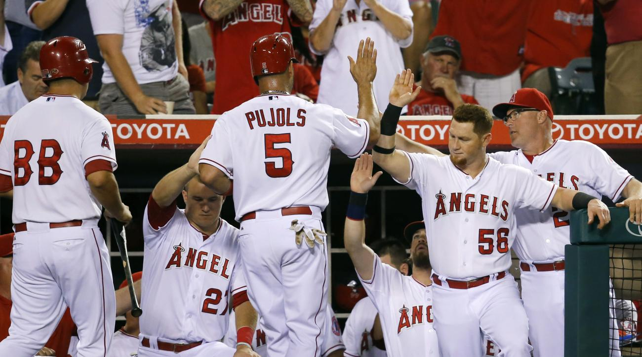 Los Angeles Angels' Albert Pujols, center, is greeted by teammates after he scored on a single hit by David Freese during the fourth inning of a baseball game against the Oakland Athletics, Tuesday, Sept. 29, 2015, in Anaheim, Calif. (AP Photo/Jae C. Hong