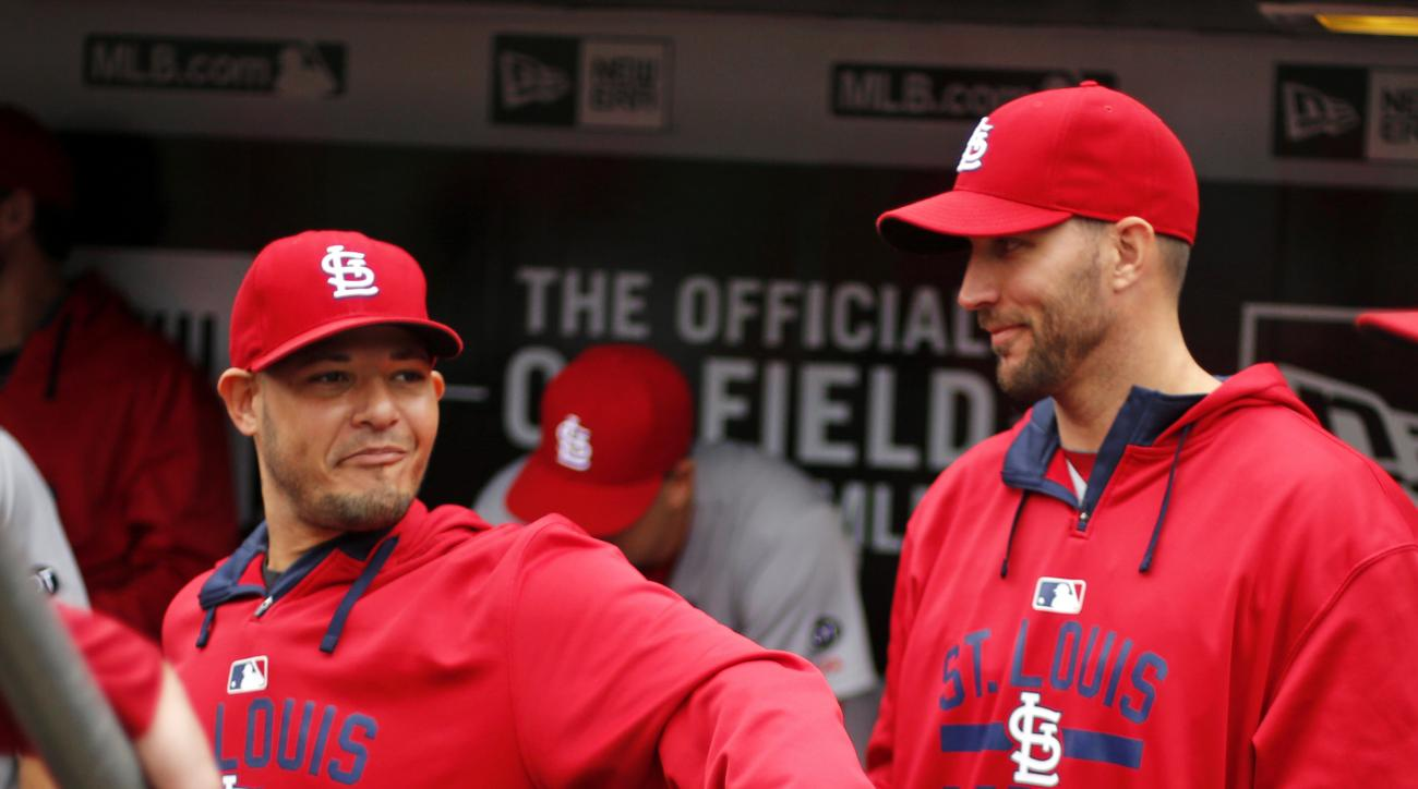 Injured St. Louis Cardinals catcher Yadier Molina, left, talks to starting pitcher Adam Wainwright in the dugout before a baseball game against the Pittsburgh Pirates in Pittsburgh, Wednesday, Sept. 30, 2015. (AP Photo/Gene J. Puskar)