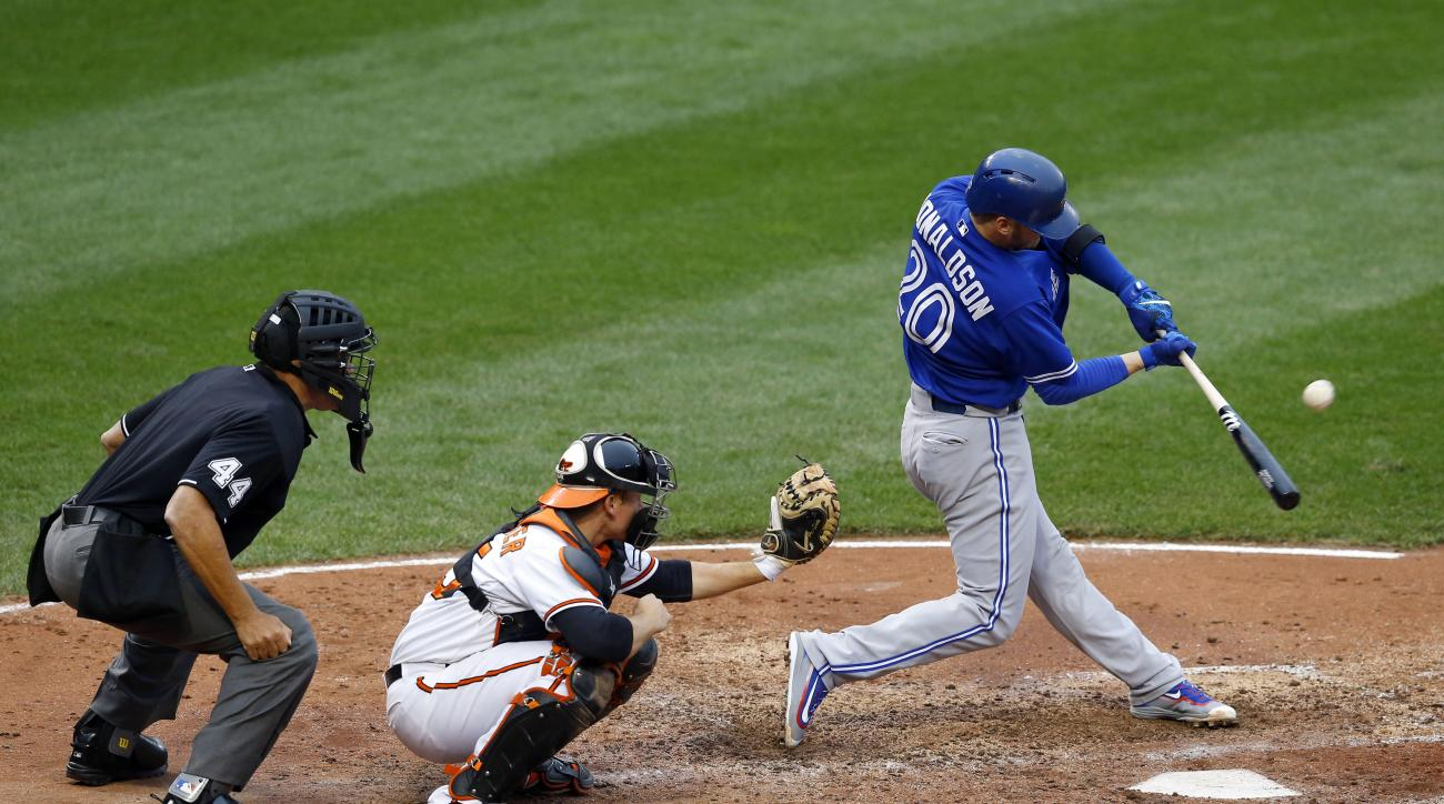 Toronto Blue Jays' Josh Donaldson doubles in front of Baltimore Orioles catcher Steve Clevenger and home plate umpire Kerwin Danley in the fifth inning in the first baseball game of a doubleheader, Wednesday, Sept. 30, 2015, in Baltimore. Ben Revere score