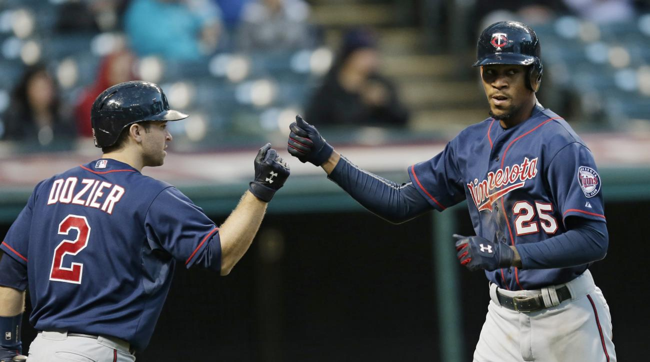 Minnesota Twins' Byron Buxton (25) is congratulated by Brian Dozier (2) after Buxton hit a solo home run off Cleveland Indians relief pitcher Shawn Armstrong in the ninth inning of the first baseball game of a doubleheader, Wednesday, Sept. 30, 2015, in C